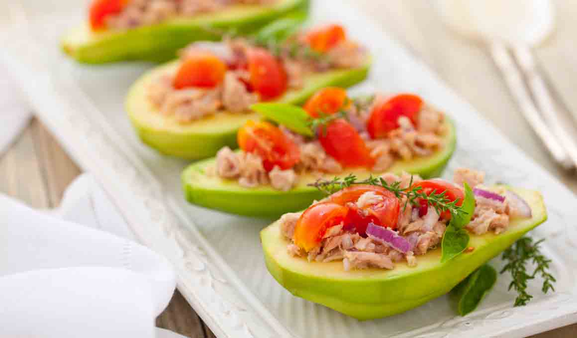 Cena fitness de aguacates rellenos de atún, tomate y anchoas