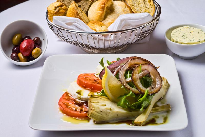Ensalada templada de alcachofas, cebollas, rúcula, tomate y queso fresco